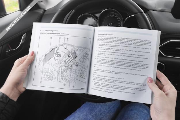 Libro abierto en la mano de la niña en una maqueta del salón del automóvil