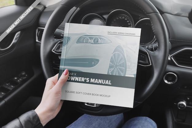 Libro cuadrado en la mano de la niña en la maqueta del volante del automóvil