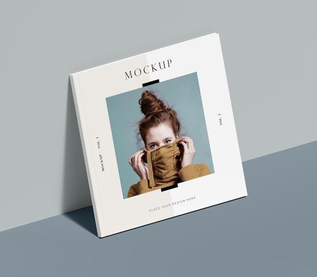 Libro cuadrado con maqueta de revista editorial de mujer apoyada en la pared