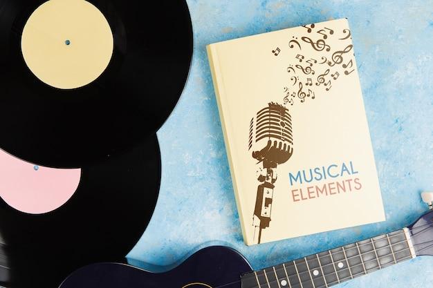 Libro de elementos musicales con guitarra de vinilo y ukelele