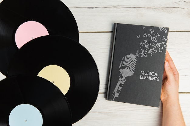 Libro de elementos musicales con vista superior de discos de vinilo