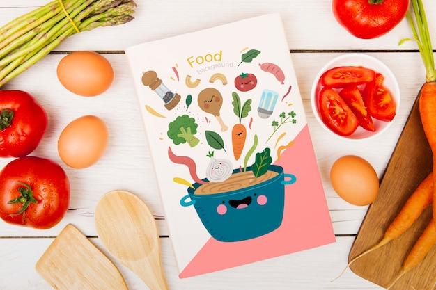 Libro de menú de comida rodeado de huevos y tomates.
