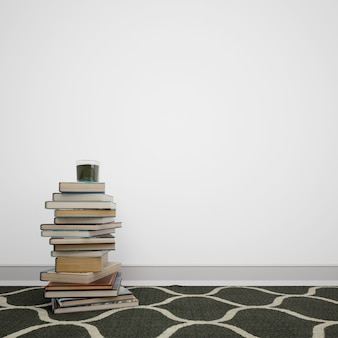 Libros apilados en el piso al lado de la pared blanca con copyspace