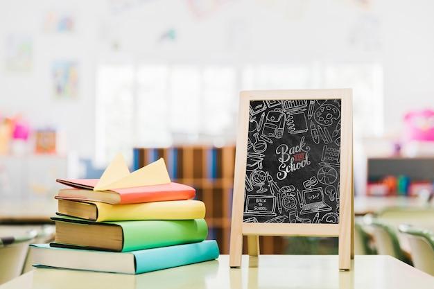 Libros coloridos junto a la maqueta de pizarra de la escuela