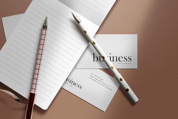Limpie la maqueta de tarjeta de visita mínima debajo del cuaderno con bolígrafo