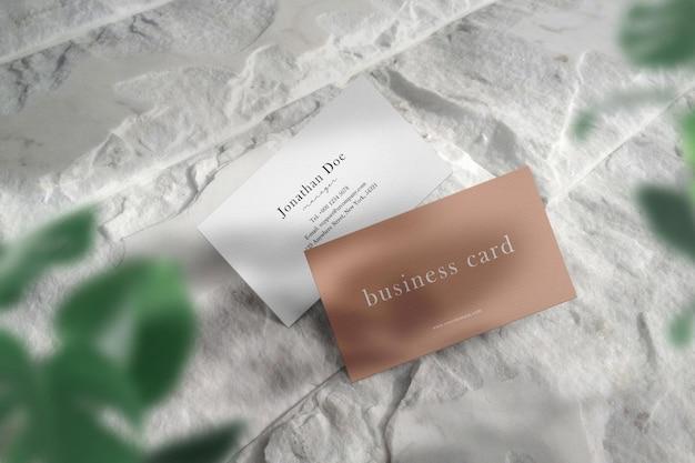 Limpie la maqueta de la tarjeta de visita mínima en el piso de piedra blanca y la sombra clara.