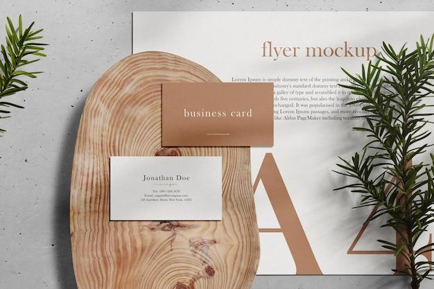 Limpie la tarjeta de visita mínima y la maqueta a4 en un plato de madera con coníferas