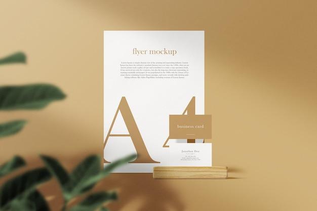 Limpie la tarjeta de visita mínima y la maqueta de papel a4 en madera con fondo de hojas. archivo psd.