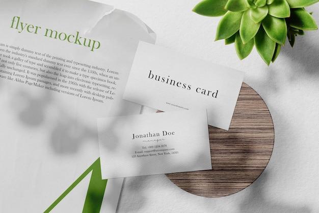 Limpie la tarjeta de visita mínima y la maqueta de papel a4 en un plato de madera con planta