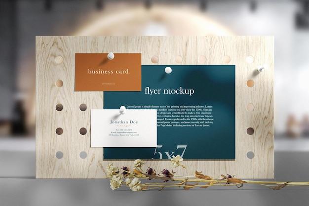 Limpie la tarjeta de visita mínima y la maqueta de volante en una tabla de madera con hojas secas en la cafetería