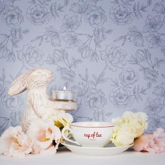 Lindo arreglo con taza de té y flores.