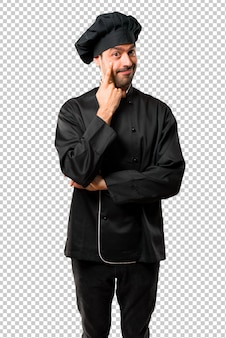 Lo chef in uniforme nera in piedi e guardando in avanti aprendo l'occhio con il dito