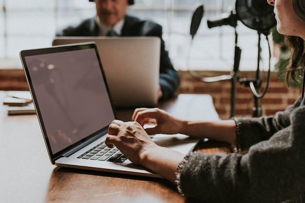 Locutor en un estudio usando una maqueta de pantalla de computadora portátil
