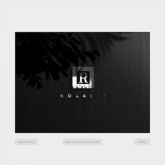 Logo plateado en pared negra con sombras