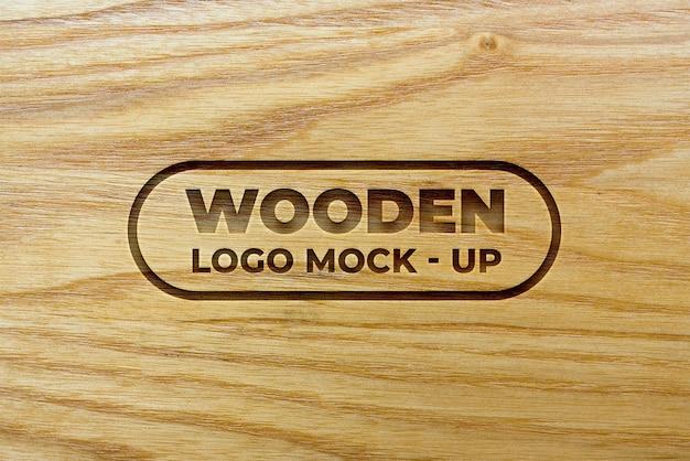 Logomodel met gegraveerd effect op houten achtergrondtextuur