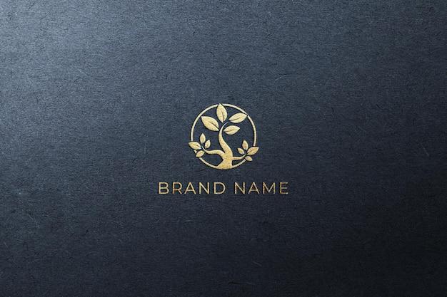 Logotipo dorado en una maqueta de papel azul oscuro