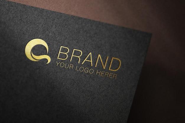 Logotipo dorado en una maqueta de papel negro