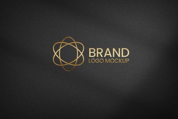 Logotipo dorado sobre maqueta de papel con textura negra