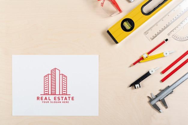 Logotipo inmobiliario con edificios y artículos de papelería