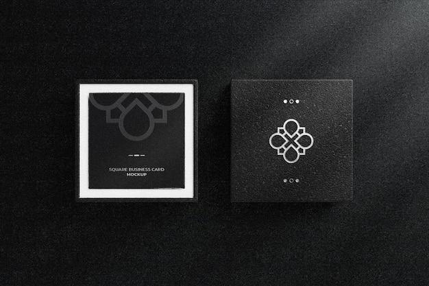 Logotipo de lámina plateada en caja de cuero negro con maqueta de tarjeta de visita cuadrada