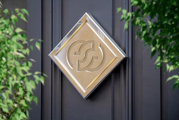 Logotipo de letrero metálico en maqueta de pared