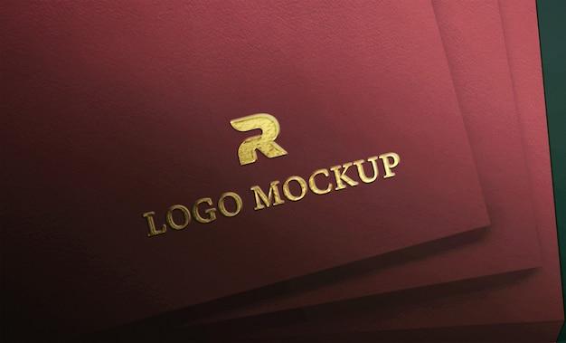 Logotipo de luxuy gold en relieve en maqueta de papel con textura roja