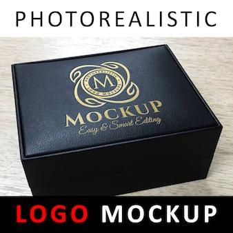 Logotipo de la maqueta: logotipo dorado de debossed en caja de cuero con joyería negra