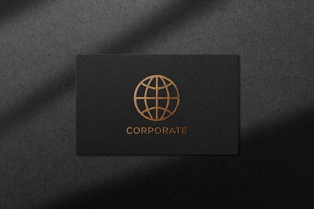 Logotipo de maqueta en relieve dorado sobre textura de papel negro