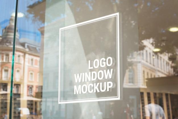 Logotipo, maqueta de signo en la ventana de cristal de la tienda. edificios de la ciudad en segundo plano