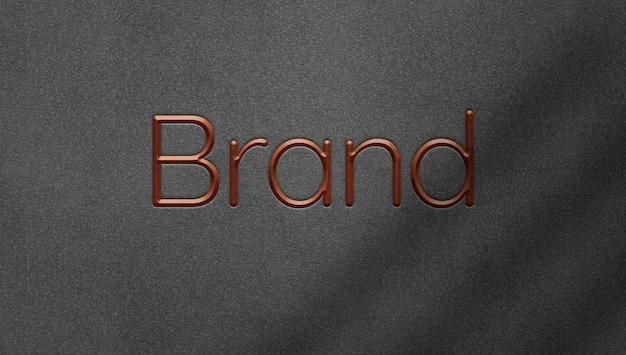 Logotipo metálico grabado sobre fondo de fieltro