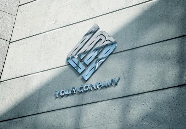 Logotipo metálico reflectante en la maqueta de la fachada del edificio