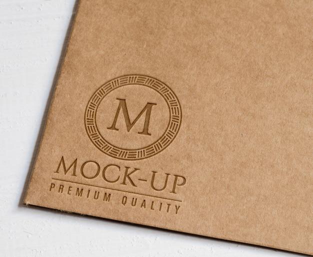 Logotipo en relieve sobre papel marrón rústico.