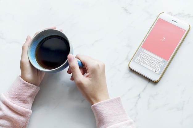 Luchtmening van vrouw met een hete kop van koffie en een smartphone