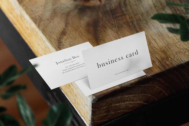 Maak een minimaal mockup voor visitekaartjes op de bovenste houten tafel met bladeren schoon