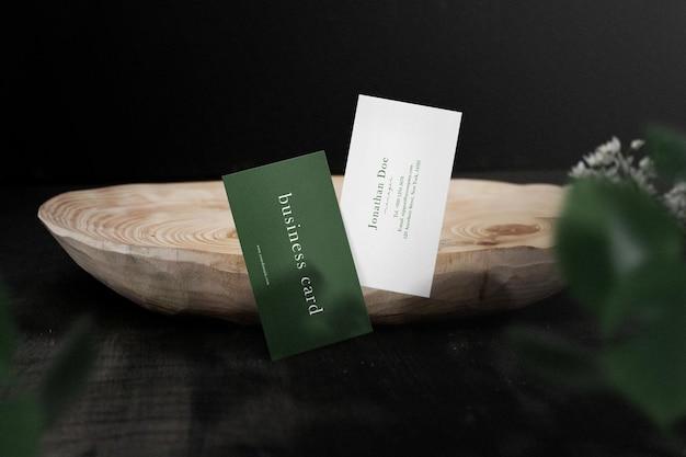 Maak een minimaal visitekaartjemodel op een houten zijplaat met bladeren schoon