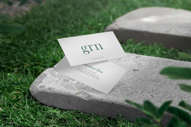 Maak een minimaal visitekaartjemodel schoon op de achtergrond van de grasplaat.