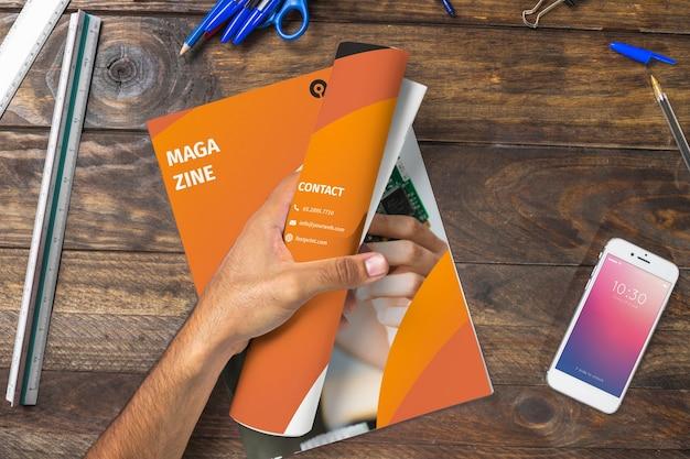 Magazine e smartphone mockup sul tavolo in legno con penne e righelli