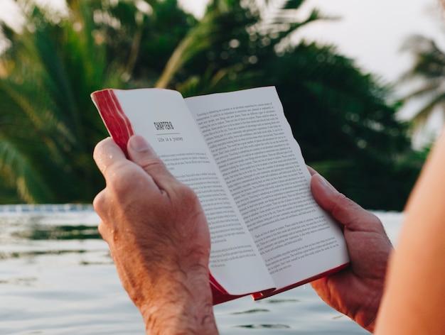 Man die een boek leest in het zwembad