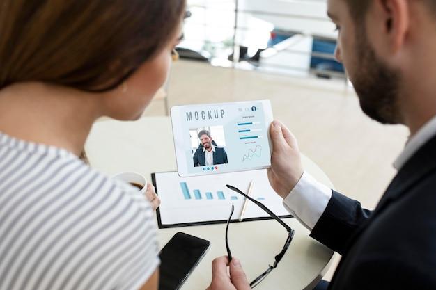 Man en vrouw die een tablet op het werk bekijken