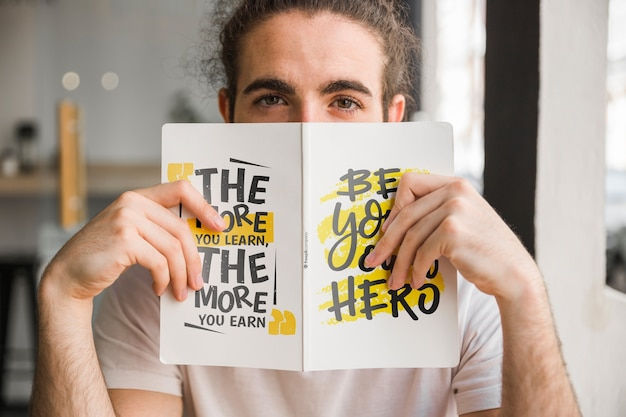 Man holding book cover mockup davanti al viso