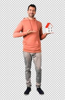 Man in een roze sweatshirt met een klein huis