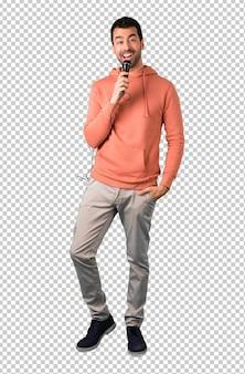 Man in een roze sweatshirt met een microfoon en zang.