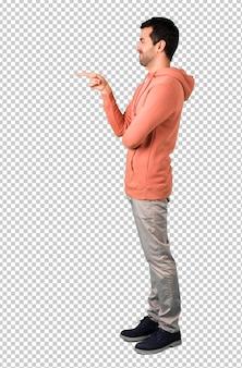 Man in een roze trui wijzende vinger opzij en presenteren van een product in zijwaartse positie