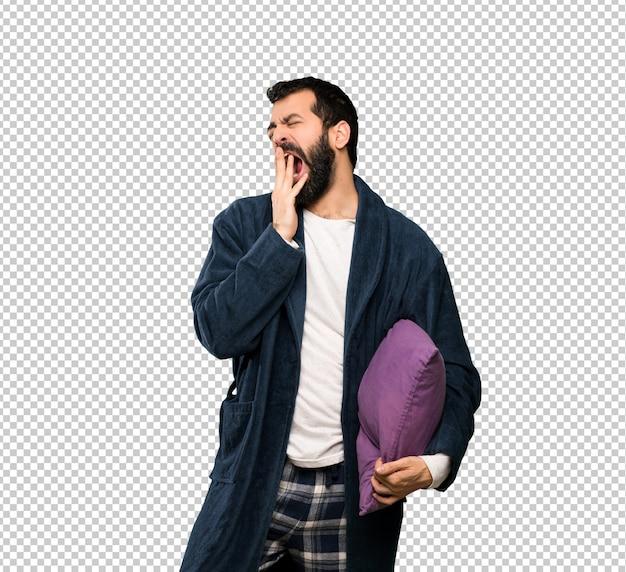 Man met baard in pyjama geeuwen en die wijd open mond met de hand