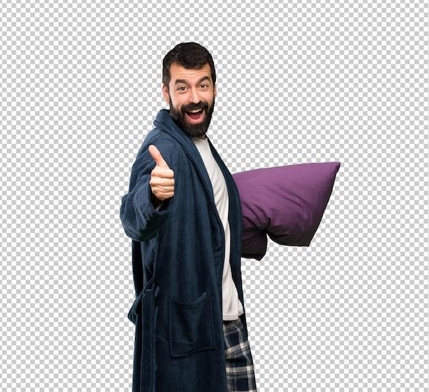 Man met baard in pyjama met duimen omhoog omdat er iets goeds is gebeurd