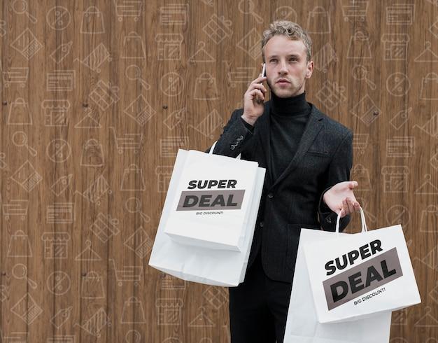 Man met boodschappentassen praten aver telefoon