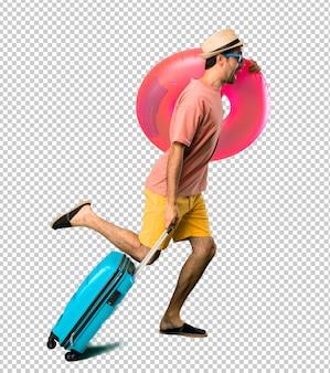 Man met hoed en zonnebril op zijn zomervakantie loopt snel