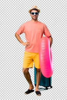 Man met hoed en zonnebril op zijn zomervakantie poseren met armen op heup en glimlachen