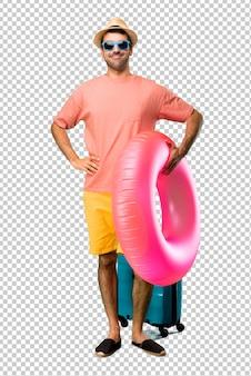 Man met hoed en zonnebril op zijn zomervakantie poseren met armen op heup en lachen op zoek naar de voorkant