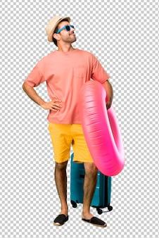 Man met hoed en zonnebril op zijn zomervakantie poseren met armen op heup en lachen